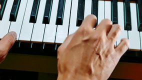 Man hands playing piano. Close-up hands of musician who plays keyboards. Male hands playing synthesizer digital piano. Man hands playing digital piano lifestyle stock footage