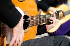 Man hands playing the Spanish guitar Stock Images