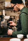 Man hands pours drink from a coffee machine. Stock Image