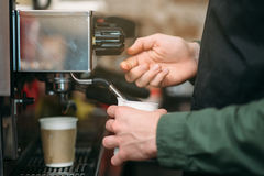 Man hands pours drink from a coffee machine. Royalty Free Stock Image