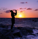 Man With Hands in Prayer. A silhouetted man stands with hands folded in praise Stock Photo
