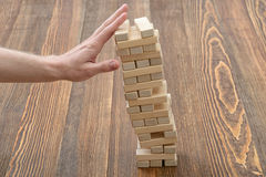 Man hands pushed the tower of bricks stock images