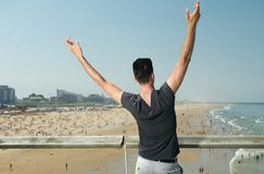 Man with hands raised overlooking beach with people Stock Photography