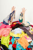 Man hands reaching out from a big pile of clothes and accessories. Man buried under an untidy cluttered woman wardrobe. Man reaching for help from to much woman