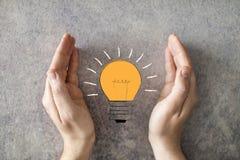 Man hands saving energy bulb light concept royalty free stock photography