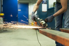 Man hands sawing metal with sparks in workshop Stock Photos