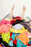 Man hands signing thumbs up reaching out from a big pile of clothes and accessories. Royalty Free Stock Photo