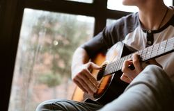 Man hands sitting on the big window windowsil and playing on guitar - fingers close up image royalty free stock photo