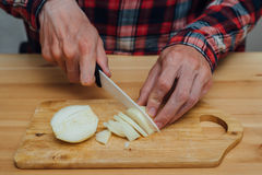 Man hands slicing fresh onnion by ceramic knife. Man hands slicing fresh onion on chopping board Royalty Free Stock Photography