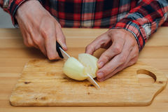 Man hands slicing fresh onnion by ceramic knife. Man hands slicing fresh onion on chopping board Stock Images