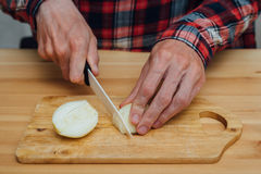 Man hands slicing fresh onnion by ceramic knife. Man hands slicing fresh onion on chopping board Stock Photos