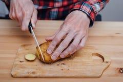 Man hands slicing fresh potato by ceramic knife Royalty Free Stock Photos
