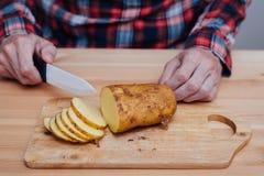 Man hands slicing fresh potato by ceramic knife Stock Image