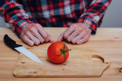 Man hands slicing fresh tomato by ceramic knife Stock Images
