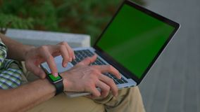 Man hands with smart watch using laptop computer green screen stock footage