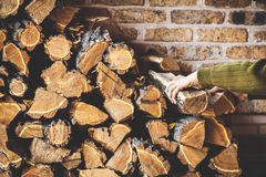 Man hands take log out of folded pile firewood stock images