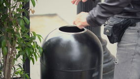 Man Hands Throwing Away Trash. Man In Black Leather Coat Visible Only By Hands Throwing Away Trash In Street Bin stock footage
