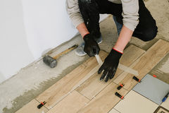 Man hands on tiles work with cement mortar Stock Photos