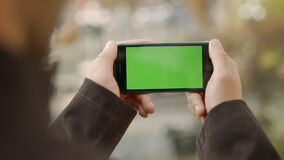 Man hands touching cellphone with greenscreen. Unknown guy holding mock up phone