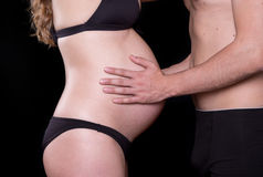 Man hands touching stomach of his pregnant woman Royalty Free Stock Image