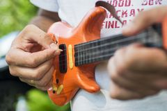 Man hands and toy electric guitar. A man plays a toy electric guitar stock photos