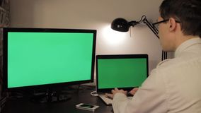 Man hands typing on green screen laptop computer. And talking on the phone stock video