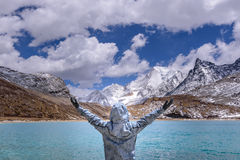 The man hands up and happy alone after arrived at the milk lake. The man hands up and happy alone after arrived at the milk lake in Yading, China Stock Photos