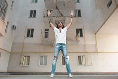 Man with hands up. Low angle shot of a urban man holding arms in the air looking up with a building on background. Stylish man understanding the power of his stock images