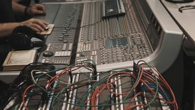 Man hands using computer mouse on music mixing console with lot of wires stock footage