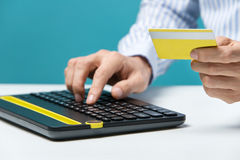 Man hands using keyboard and holding credit card with social media as Online shopping concept on blue background Stock Photography