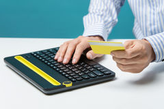 Man hands using keyboard and holding credit card with social media as Online shopping concept on blue background Royalty Free Stock Images