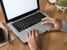 Man hands using laptop on wooden desk. Royalty Free Stock Photos