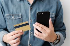 Man hands using smart phone and holding credit card, shopping on royalty free stock photography