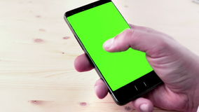 Man hands using a smart phone for write text messaging with chroma key, green screen on wood table stock video footage