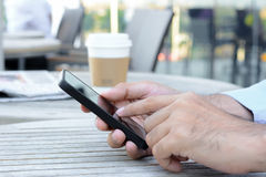A man hands using smartphone on the table with coffee cup Royalty Free Stock Photo