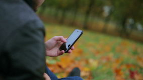 Man hands using smartphone touchpad typing sms message in autumn park sitting on the grass at the background of fallen stock video footage