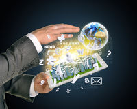 Man hands using tablet pc. Business city on touch. Screen. Earth with flying letters near computer. Elements of tgis image furnished by NASA Royalty Free Stock Photo