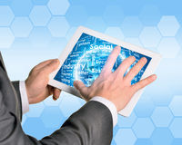 Man hands using tablet pc. Earth and business. Words on touch screen. Element of this image furnished by NASA Royalty Free Stock Images