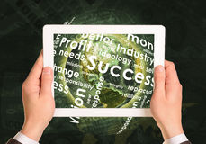 Man hands using tablet pc. Earth and business. Words on touch screen. Element of this image furnished by NASA Stock Image