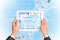 Man hands using tablet pc. Image of DNA helix on Stock Photography