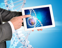 Man hands using tablet pc. Image of Earth and DNA Royalty Free Stock Photos