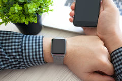 Man hands with watch and phone with a laptop Royalty Free Stock Photo