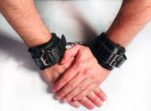 A man hands wearing black furry leather sex toy handcuffs. A man hands wearing a pair of black furry leather sex toy handcuffs for sex royalty free stock images