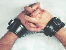 A man hands wearing black furry leather sex toy handcuffs. A man hands wearing a pair of black furry leather sex toy handcuffs for sex stock images