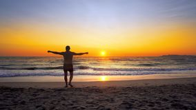 Man with hands wide open in VICTORY pose walks on empty ocean beach into water