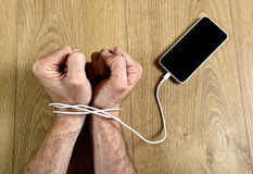Man hands wrapped on wrists with mobile phone cable handcuffed in smart phone networking addiction concept