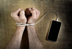 Man hands wrapped on wrists with mobile phone cable handcuffed in smart phone networking addiction concept. Man hands trapped and wrapped on wrists with mobile Royalty Free Stock Images