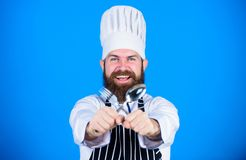Man handsome with beard holds kitchenware on blue background. Cooking process concept. Lets try dish. Hungry chef ready. To try food. Time to try taste. Chef royalty free stock image