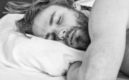 Man handsome guy lay in bed. Get adequate and consistent amount of sleep every night. Expert tips on sleeping better. Bearded man sleeping face relaxing on stock photo