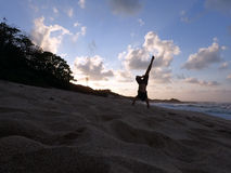 Man Handstanding on beach at sunset as wave crash Royalty Free Stock Photos